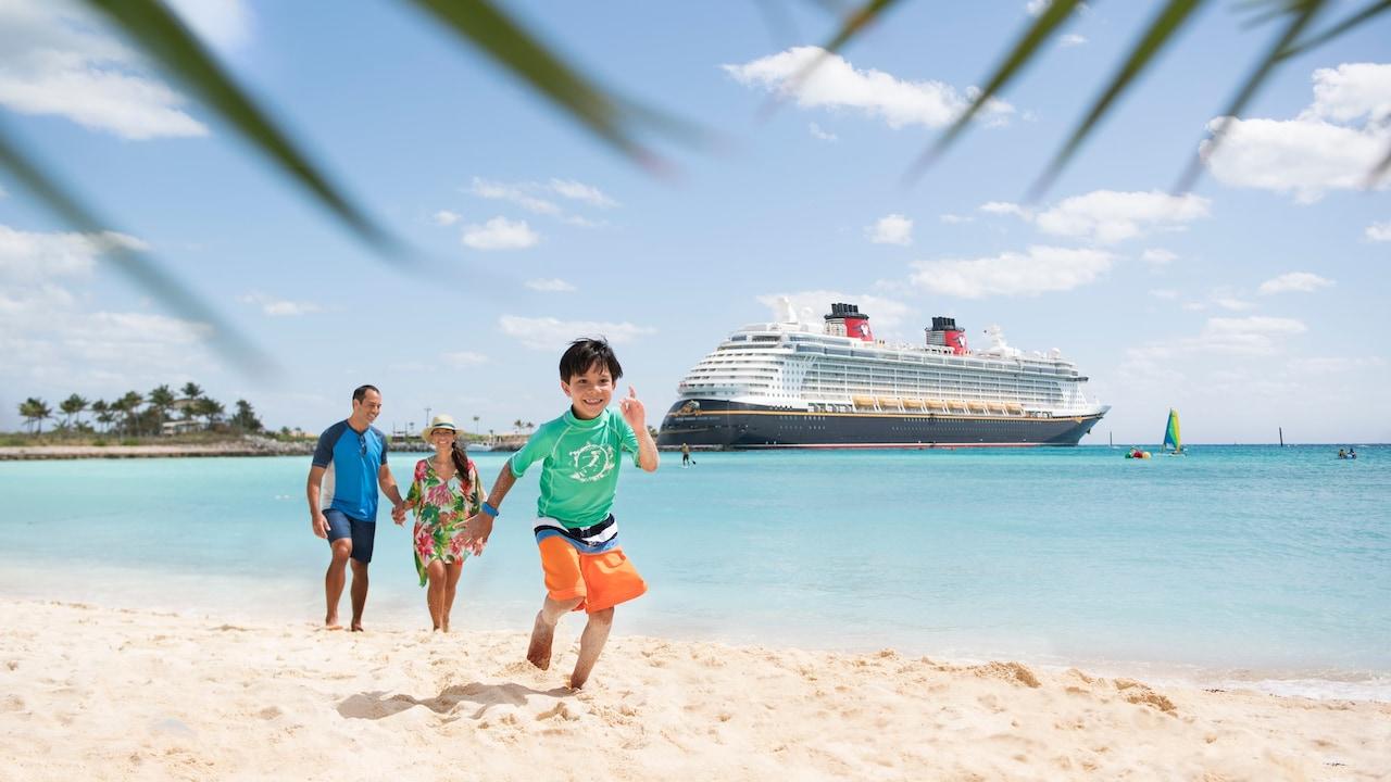 A child runs down a beach near a couple and a docked Disney Cruise Line ship