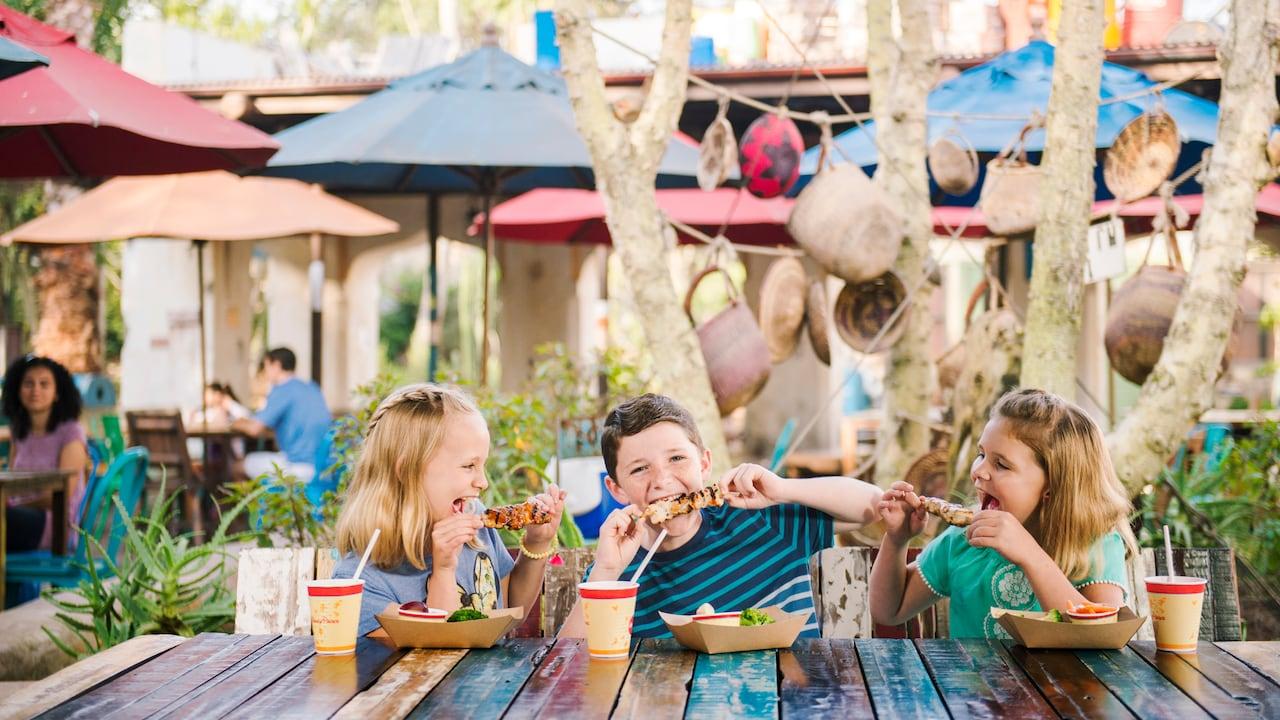 Tres niños disfrutan de kebabs y bebidas en una mesa al aire libre