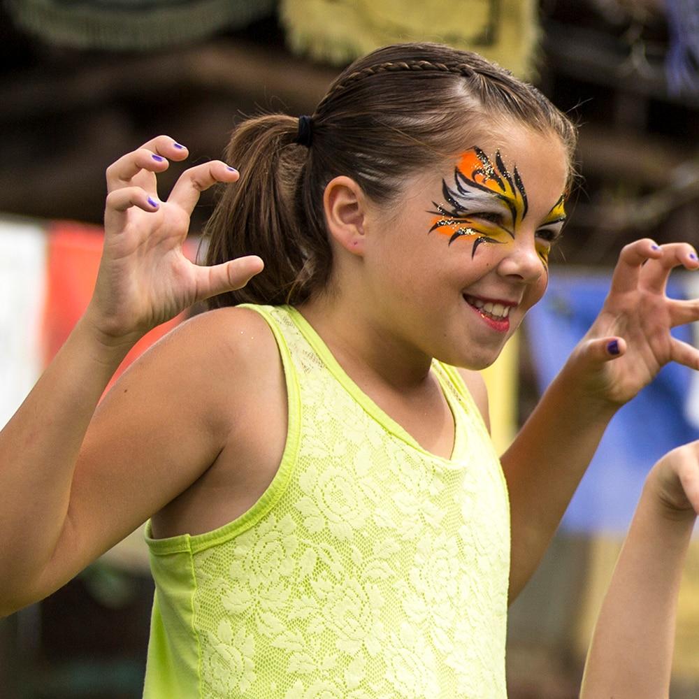 Uma jovem Hóspede com pintura facial de tema feroz sorri enquanto faz pose para uma foto