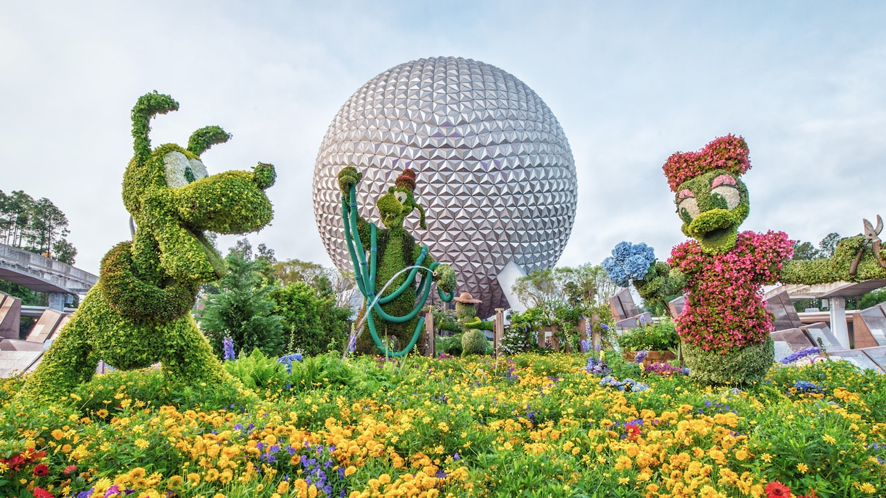 Arbustos artísticos con la forma de Daisy, Pluto y Goofy exhibidos justo en frente de Spaceship Earth en Epcot