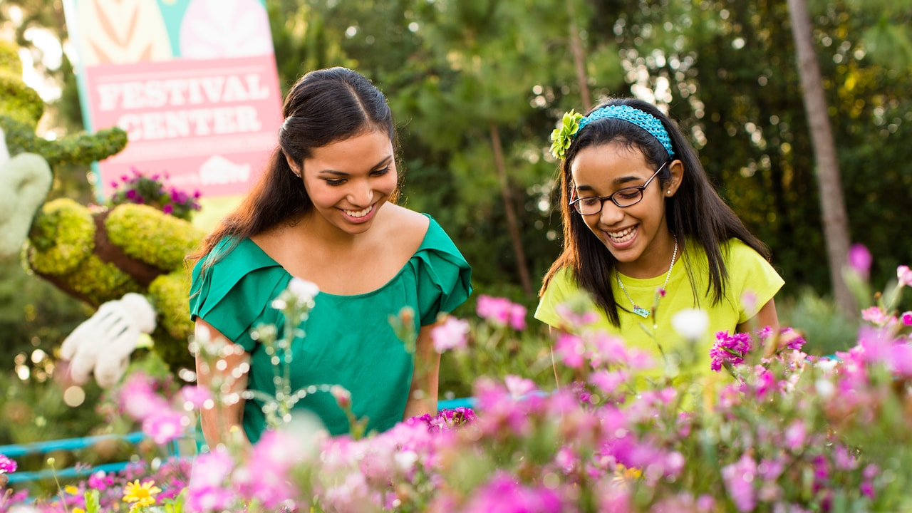 Two girls smile while gazing upon vibrant flowers at the Epcot International Flower & Garden Festival