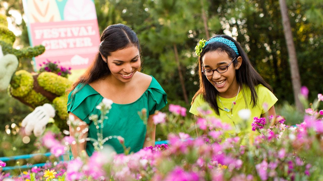 Duas meninas sorriem e apreciam flores de cores vibrantes no Epcot International Flower & Garden Festival