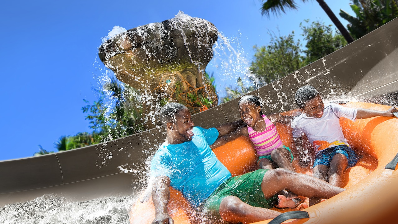 A father, son and daughter get splashed while riding on a family raft at Miss Adventure Falls.