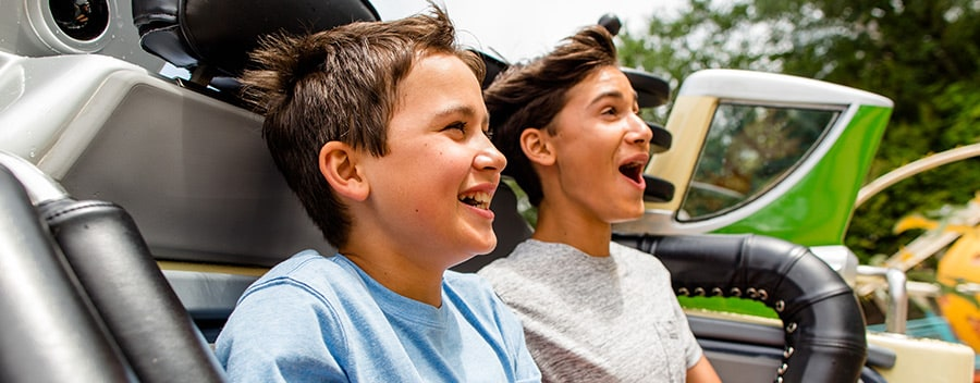 A duo of young male Guests enjoy an exhilarating ride on an attraction at Walt Disney World Resort