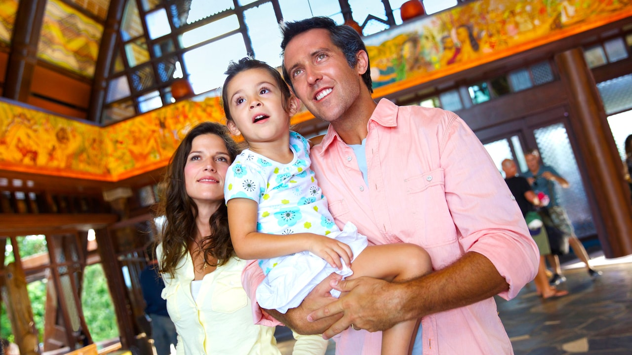 A mother and father with their young daughter stand in the main lobby at Aulani Resort and Spa