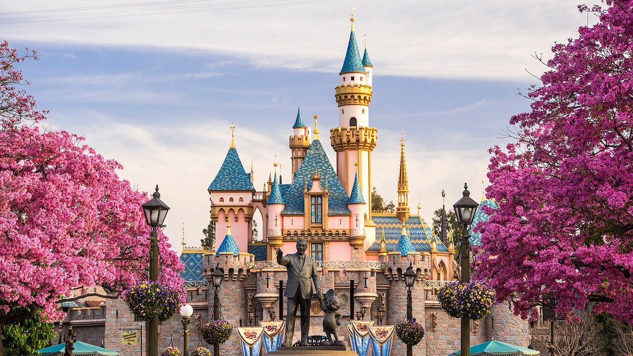 A statue of Walt Disney and Mickey Mouse stands in front of Sleeping Beauty Castle