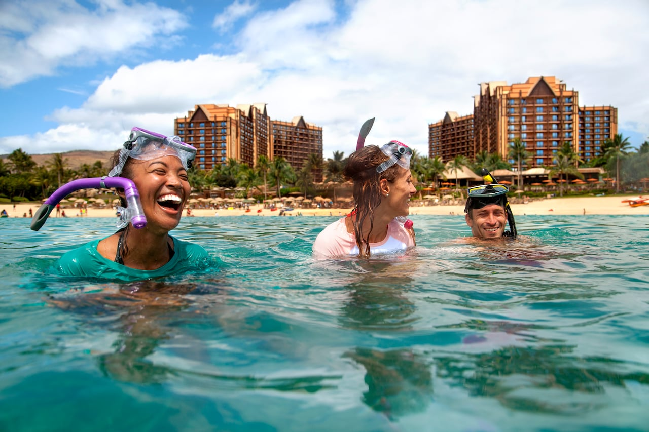 Three friends wearing snorkel masks on their heads laugh together in the water near a beach