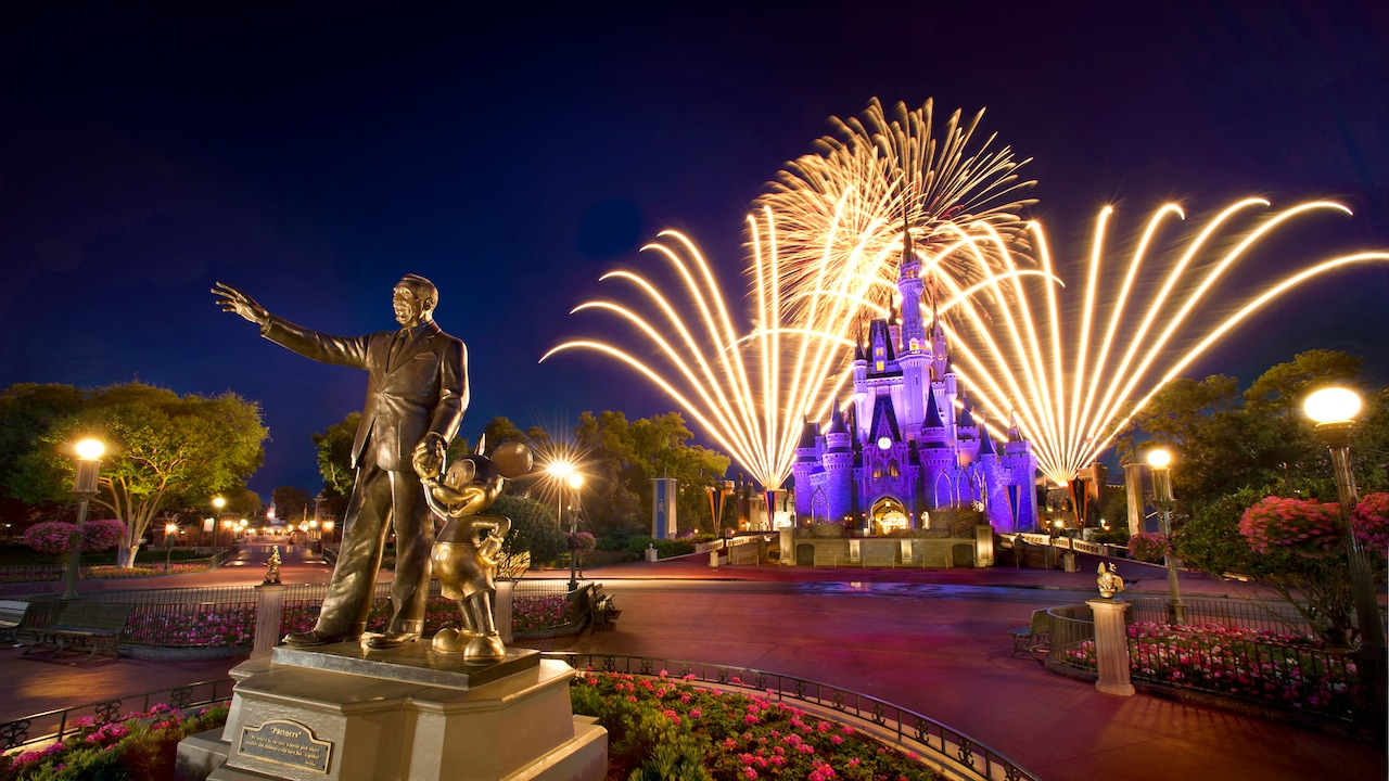 A statue of Walt Disney and Mickey Mouse stands near fireworks fanning up from Cinderella Castle