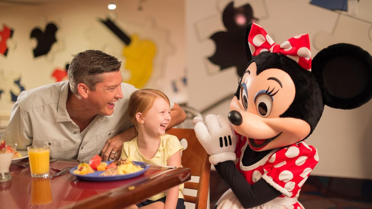 Niño y adulto sonríen, disfrutando a Minnie Mouse en una Comida con los Personajes