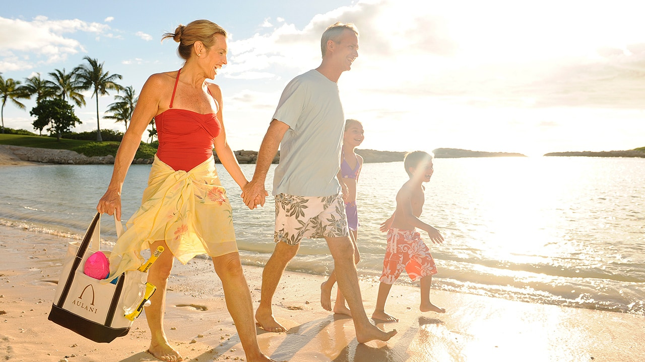 A family in swimwear walks hand in hand along the beach at Aulani Resort
