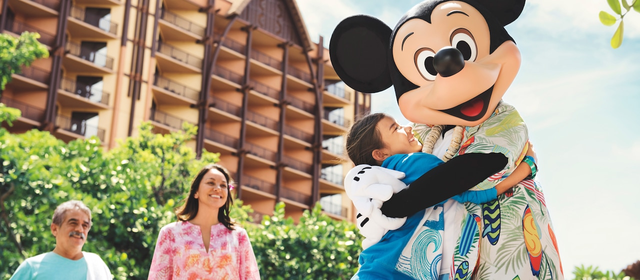 A young girl hugs a Hawaiian shirt clad Mickey Mouse, as her parents watch on smiling