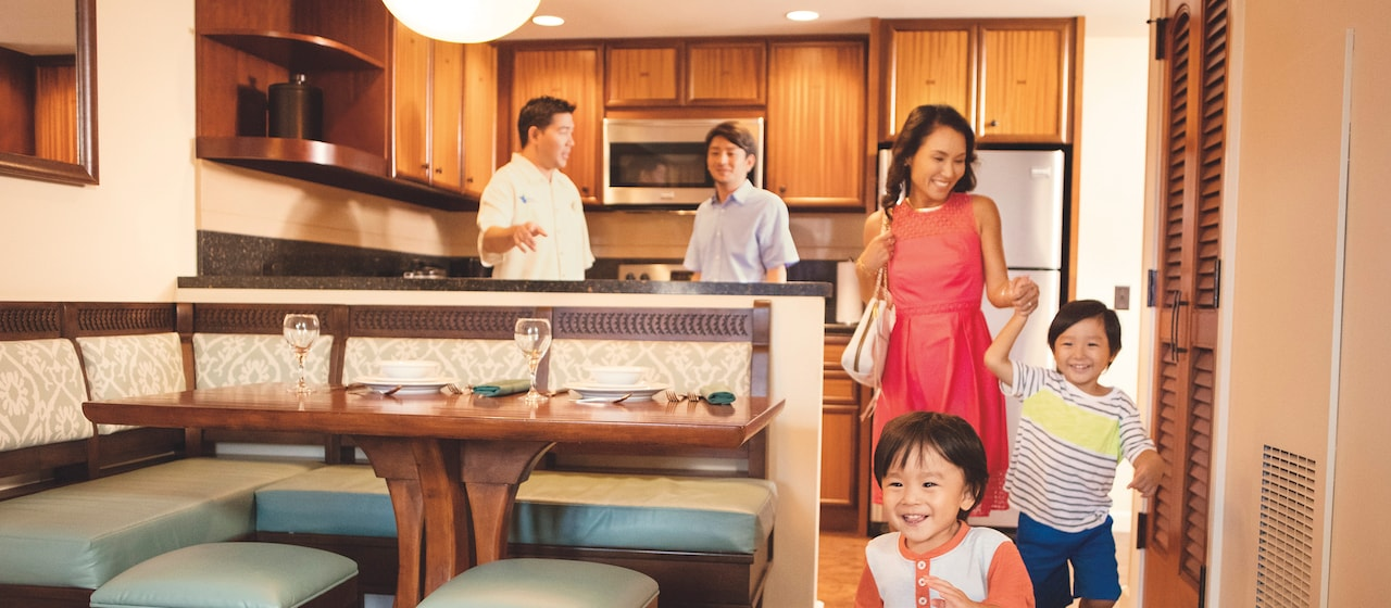 A mom and her two kids check out a villa as the dad speaks with a Disney Vacation Club Guide in the kitchen