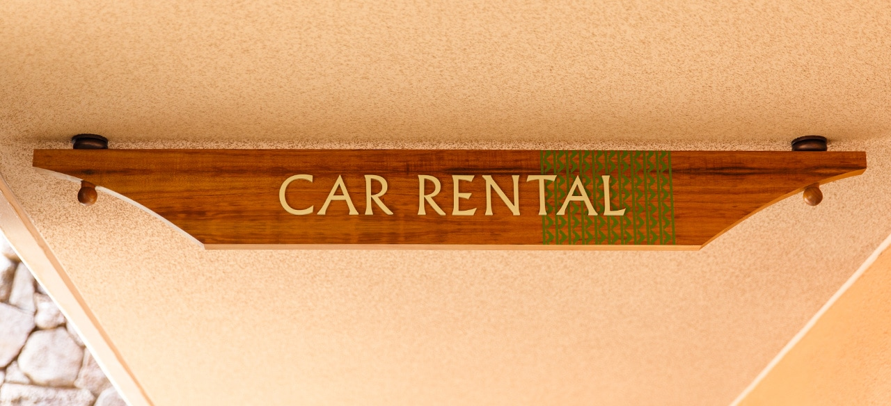 A wooden sign that reads Car Rental