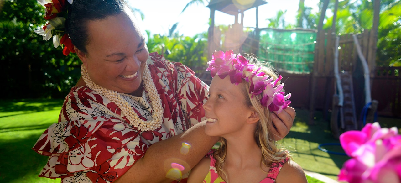 アウラニで花のレイを持つ少女とハワイの女性