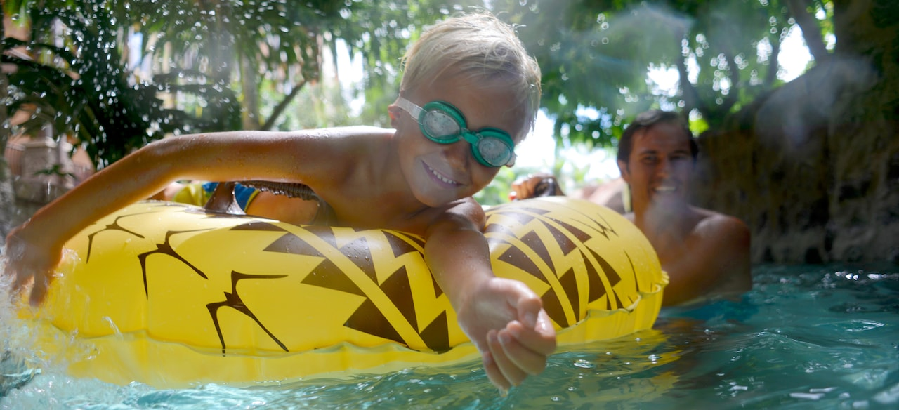 A young boy lays on an inflatable tube and floats on the Waikolohe Stream