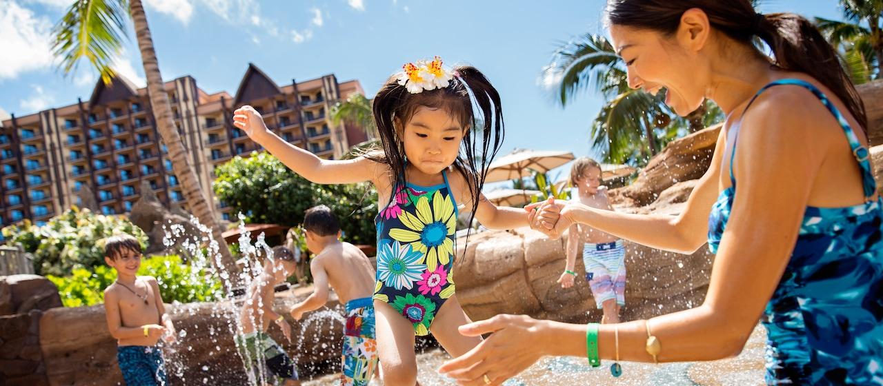 髪に花を飾り、母親の手を取り笑いながらジャンプしている少女と、ケイキ・コーヴのスプラッシュゾーンのエリアで楽しんでいる5人の子供たち。
