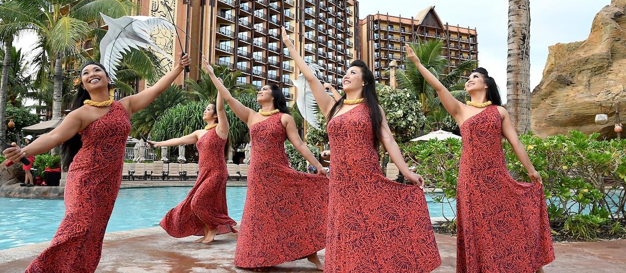 アウラ二のプールサイドで伝統的なフラを、鳥や植物の模様の入ったお揃いのドレスをきて踊る5人の女性