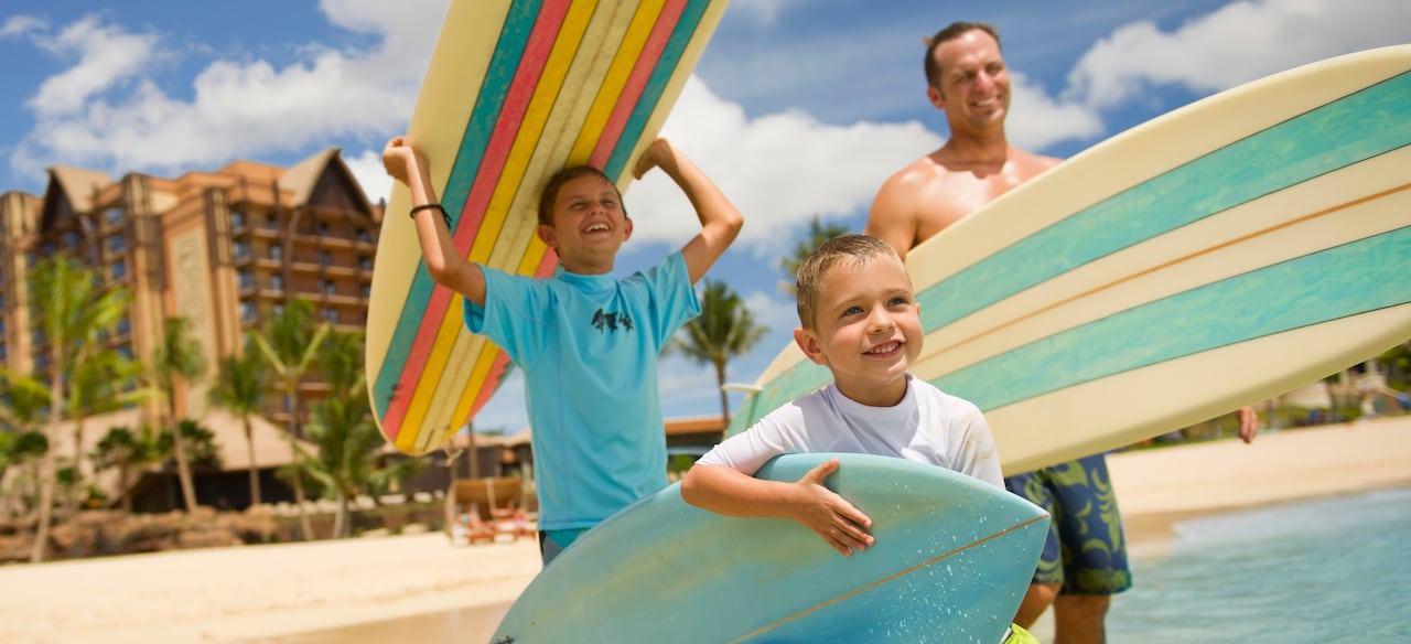 A father and his 2 young sons head toward the ocean carrying surfboards
