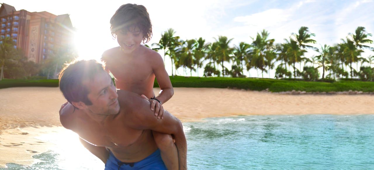 A father gives his smiling young son a piggyback ride on the shores of a tropical beach