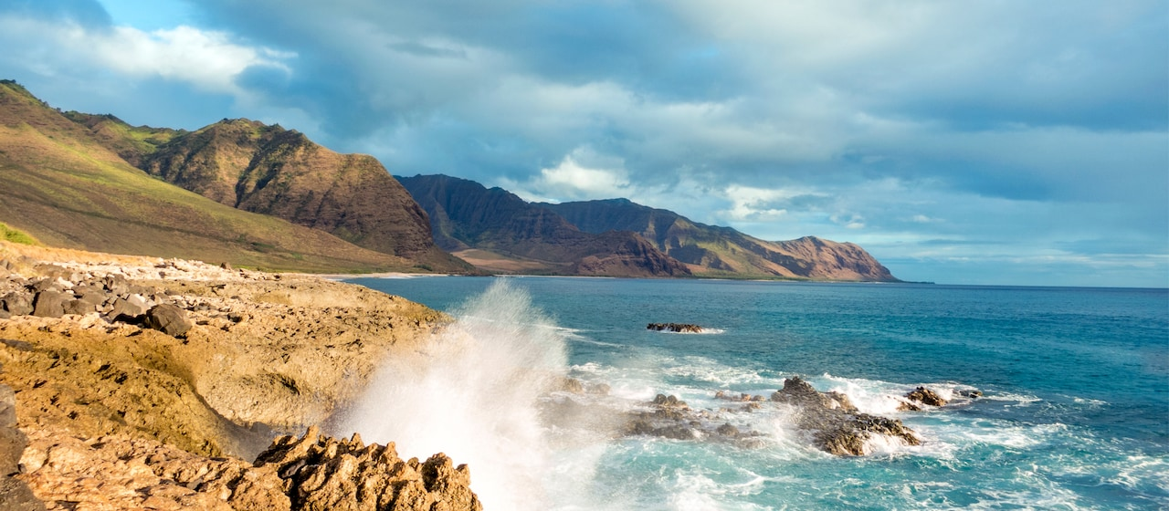 A cove along the coastline of Oahu surrounded by rugged hills.