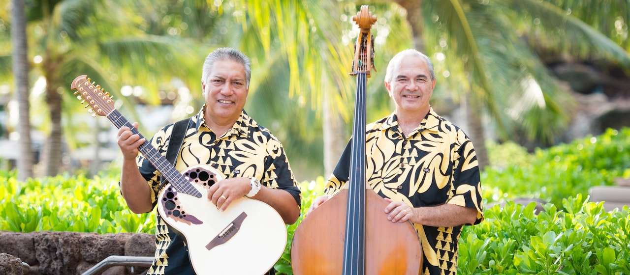 Musical duo Hema Pa'a musicians Baba Alimoot holds his guitar next to Chris Kamaka, who stands next to his stand-up bass wearing matching Aloha shirts