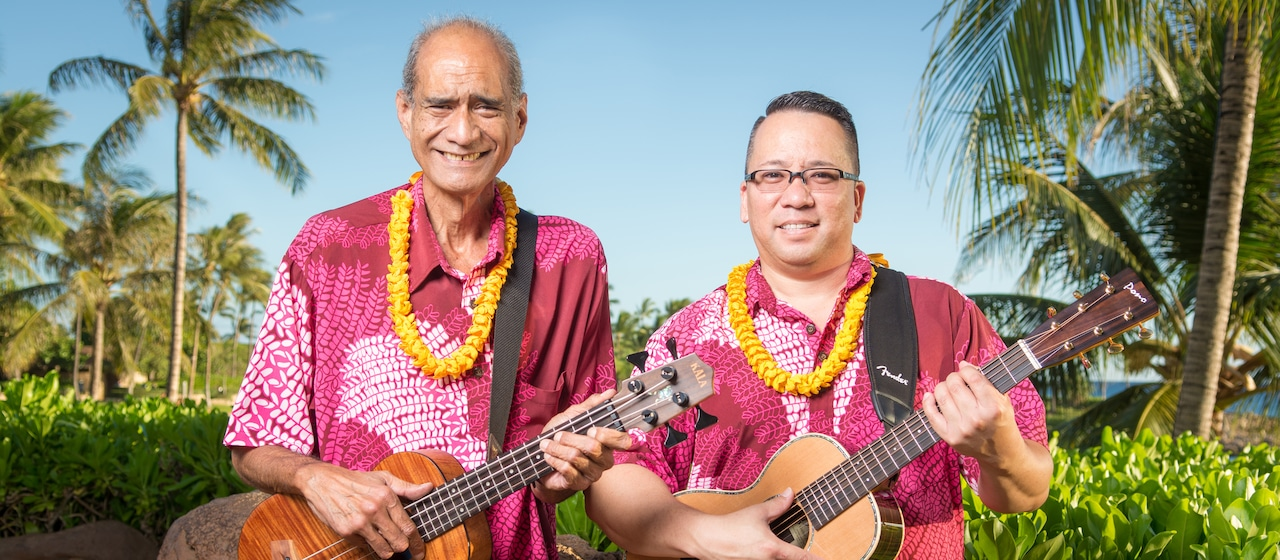 Musician and storyteller Hoku Zuttermeister, in Aloha shirt and lei, holds a ukulele and stands beside a man holding a guitar wearing a matching shirt and lei