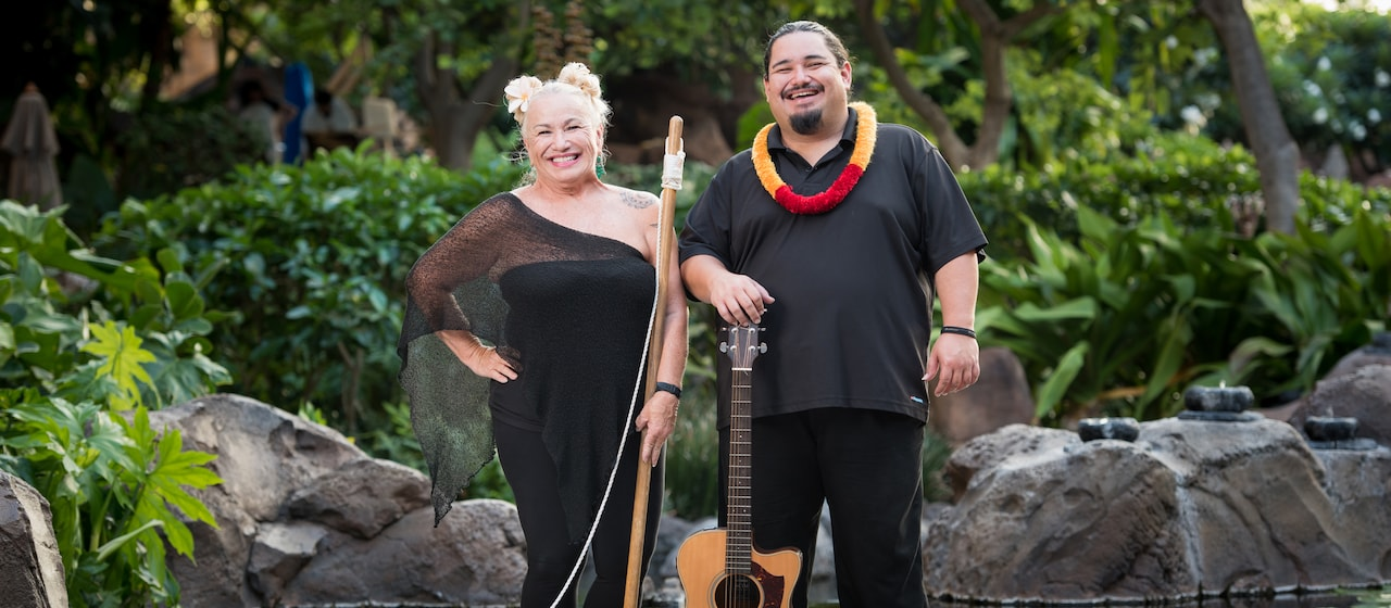 Sonny Kapu smiles and rests his hand on guitar while standing beside his mother, Marsha, who holds her washtub bass