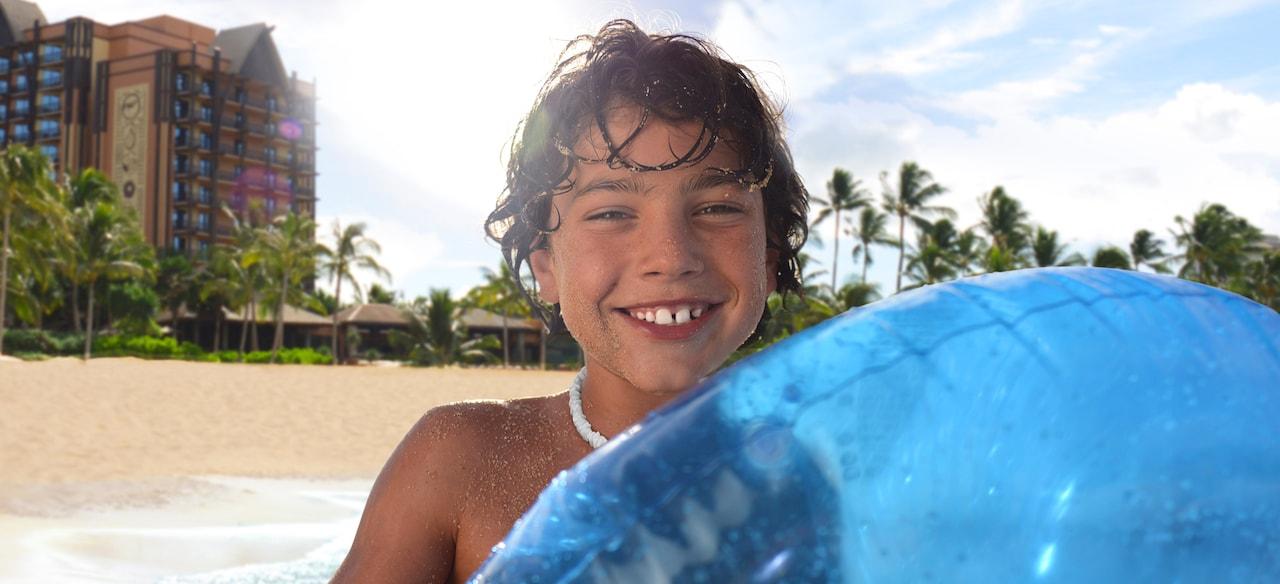 アウラニ・リゾートの海へと歩いていく青い浮き輪を持った少年