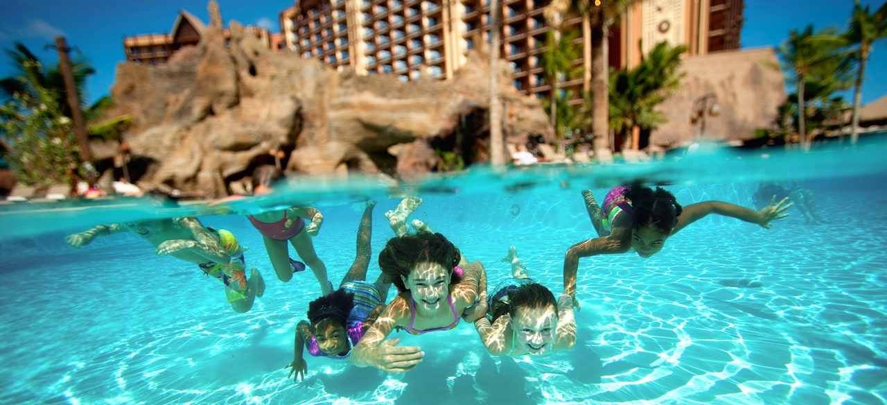 Four Girls Swim Underwater Together In A Pool With Rock Caves And Palm Trees While
