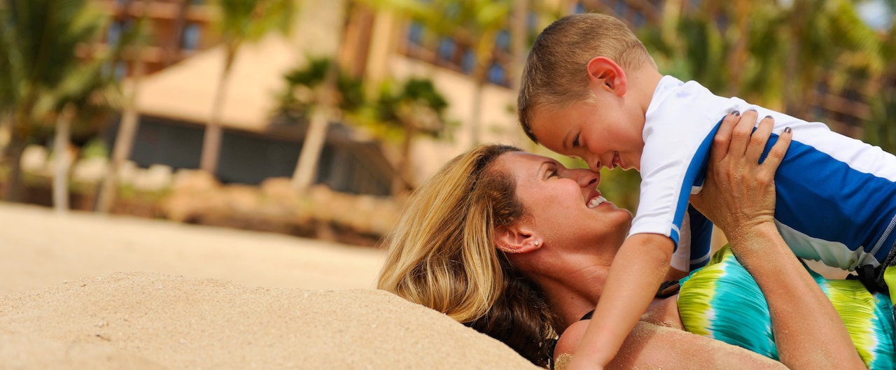 A smiling mother plays with her son on the sandy beach as palm trees sway in the background.