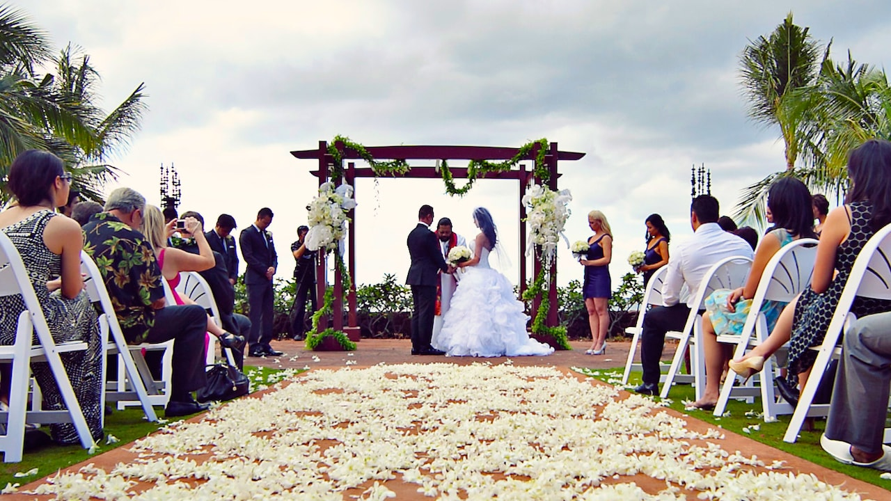 A bride and groom stand at the altar on ʻAmaʻama Patio as their guests and wedding party look on