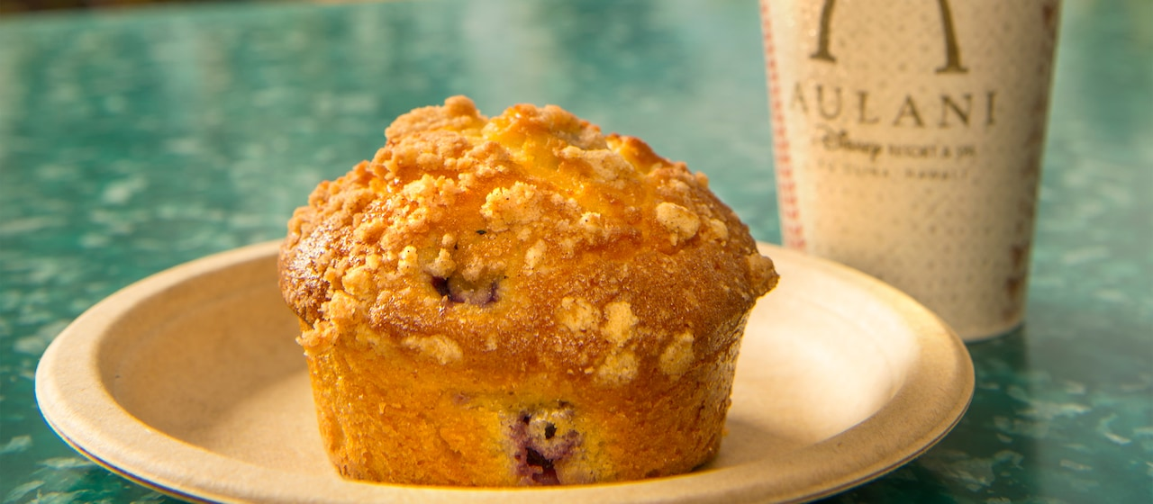 A blueberry muffin with a crumb topping on a plate beside a cup bearing the Aulani logo