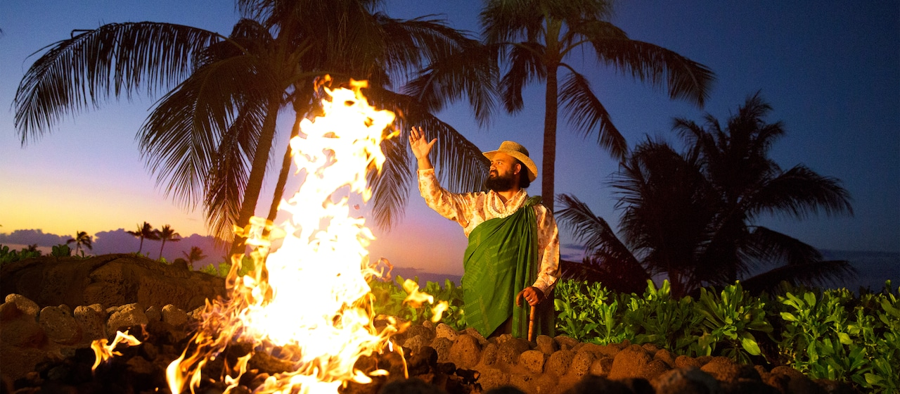 A man surrounded by palm trees performs a ceremony near a bonfire at sunset