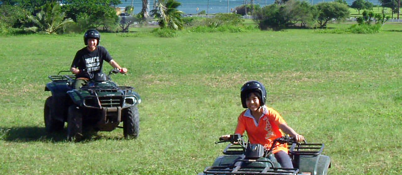 A teen boy and teen girl riding all terrain vehicles across a field