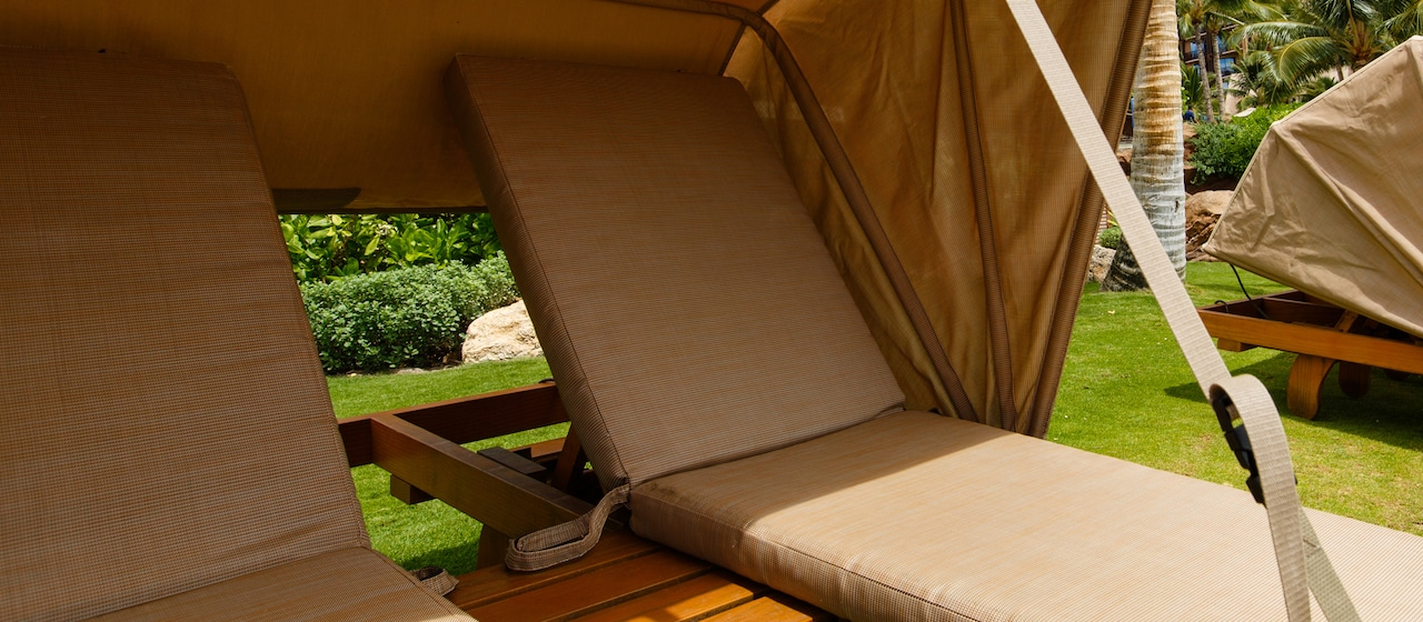 Four 2 person Casabella loungers with awnings on a lawn bordered by palm trees