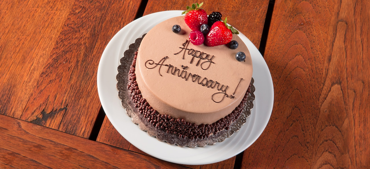 """A chocolate cake garnished with berries and ringed with chocolate morsels reads """"Happy Anniversary"""""""