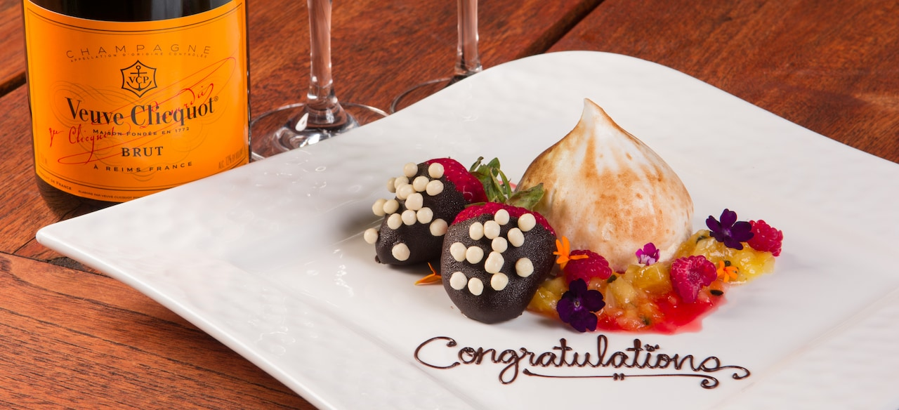"""""""Congratulations"""" is written in chocolate on a plate of confections beside a bottle of champagne."""