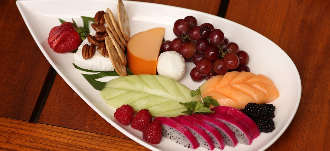 A platter features a cheese arrangement surrounded by slices of berries, melons and other fruits