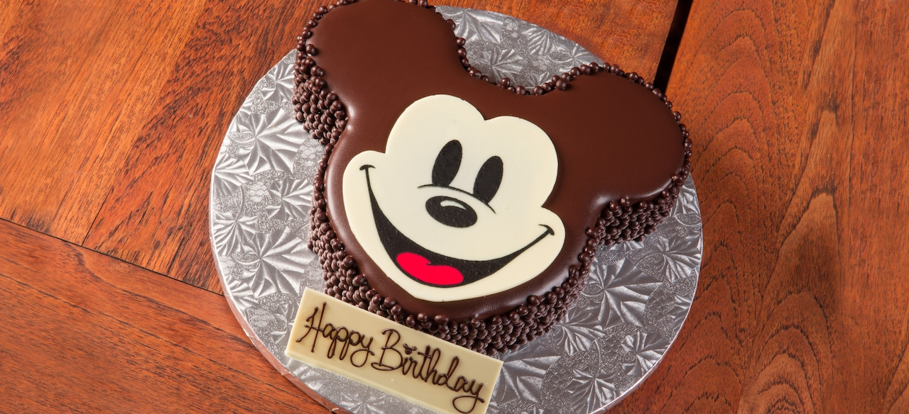 """A chocolate cake shaped and decorated like Mickey Mouse with an inscription reading """"Happy Birthday"""""""