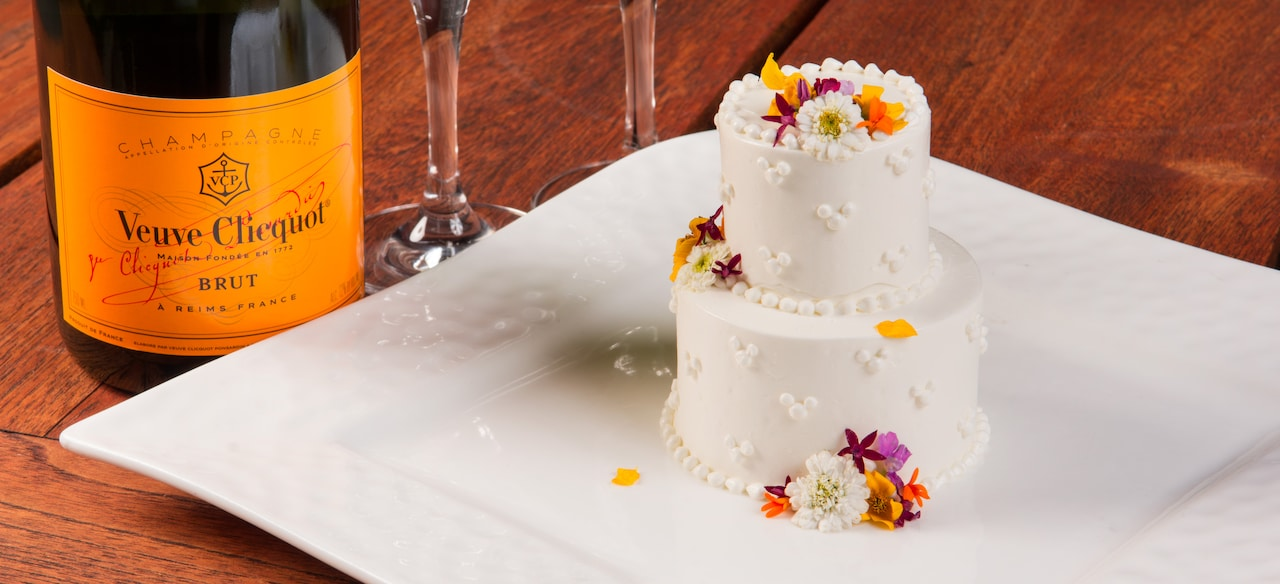 An elegantly decorated 2-tier iced mini cake served on a platter beside a bottle of Champagne.