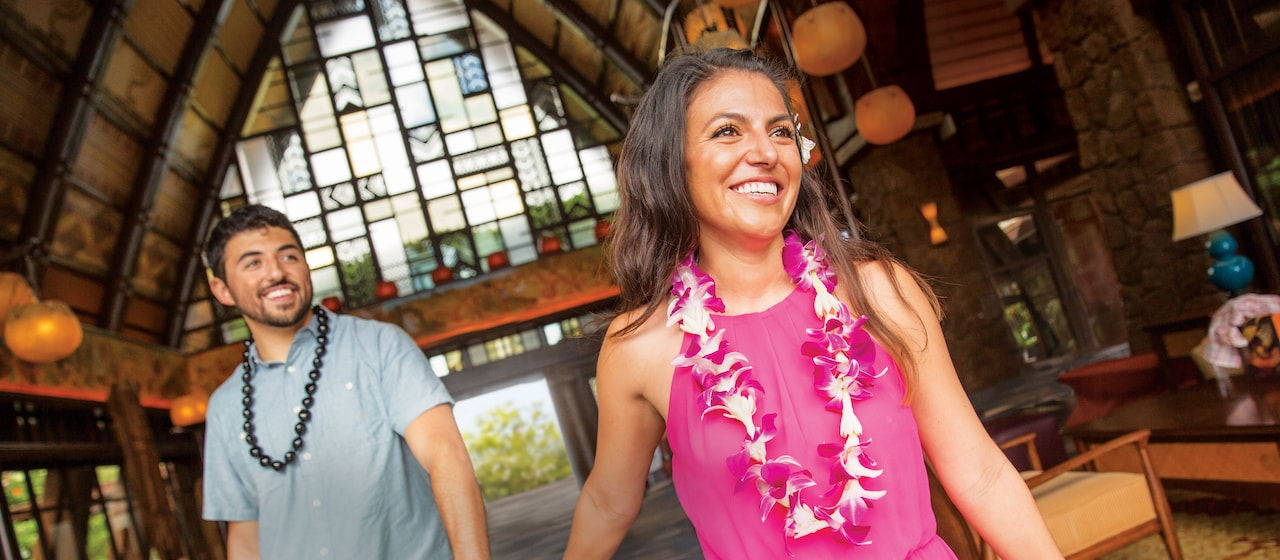 A smiling young couple wearing leis walks hand in hand through the lobby of the Aulani Resort