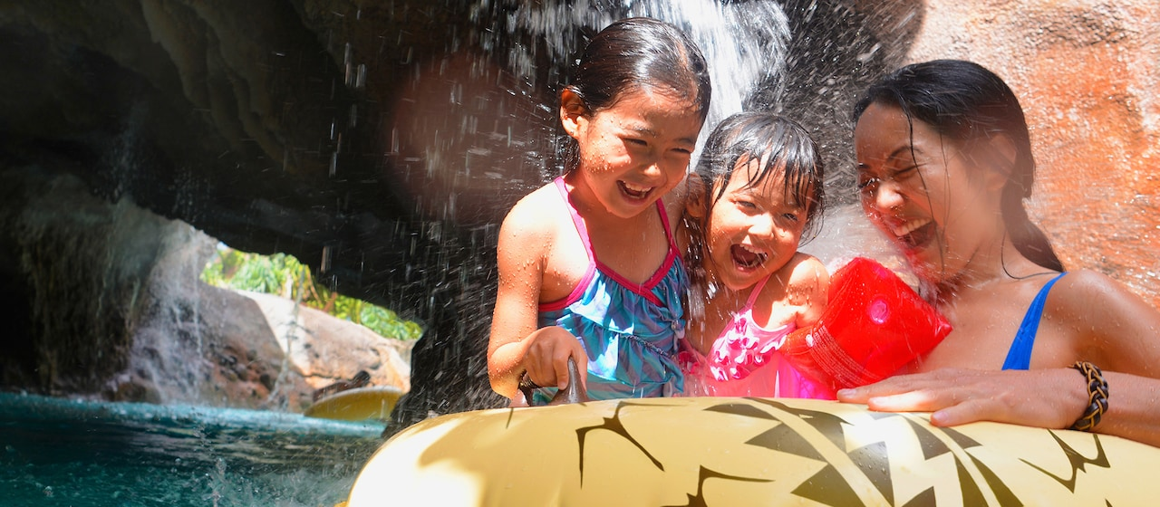 浮き輪に乗ってワイコロヘ・ストリームの滝の下へ漂いながら、楽しそうに笑う母親と 2 人の娘たち