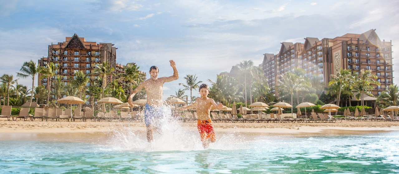A father and his son running into the lagoon, with the beachfront and towers of Aulani Resort behind them