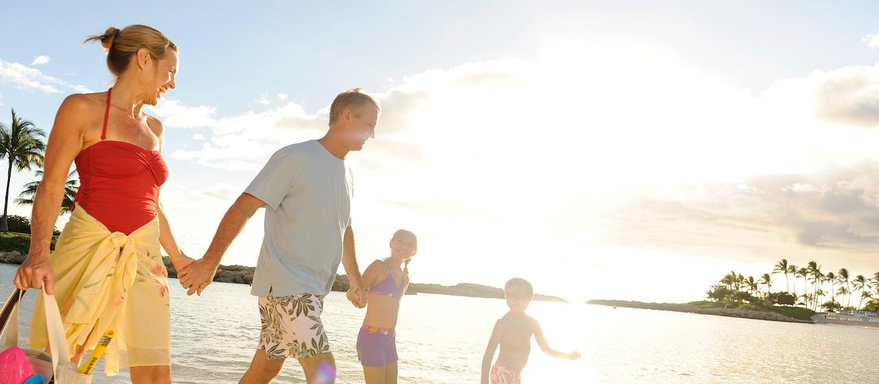 A family walks on Ko Olina Beach at Aulani