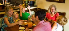 A family in the dining area of a villa at Aulani