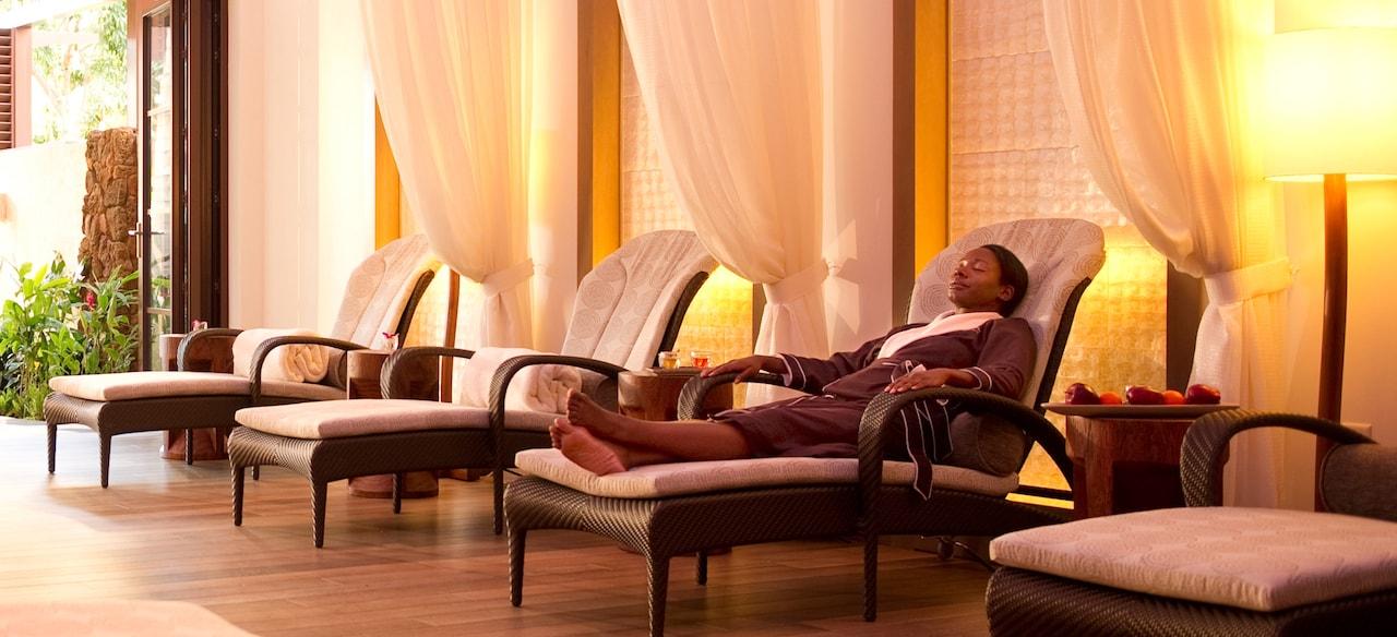 壁に沿って置かれたラウンジ・チェアと白いドレープがあるラウンジの椅子でくつろぐスパ・ローブを着た女性