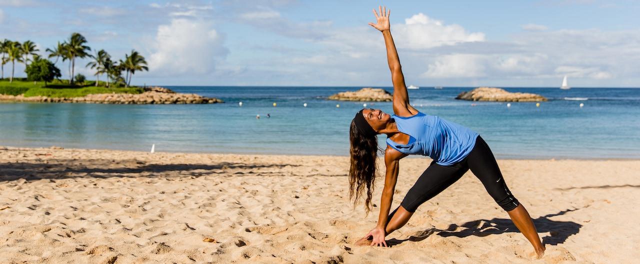 ビーチで三角のポーズをとるいきいきとした女性のヨガ・インストラクター