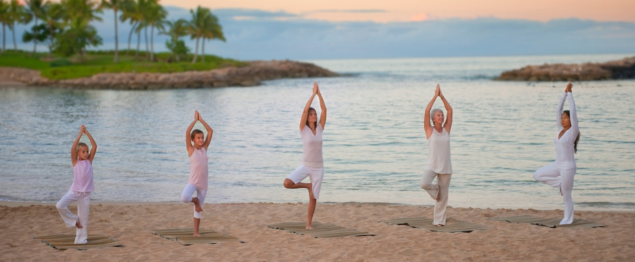 ビーチでのヨガのクラスで、木のポーズをとる 2 人の少女とさまざまな年齢の 3 人の女性