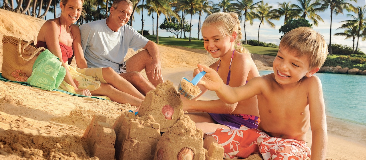 ビーチで砂のお城を作る笑顔の子供たちとそれを見ている両親