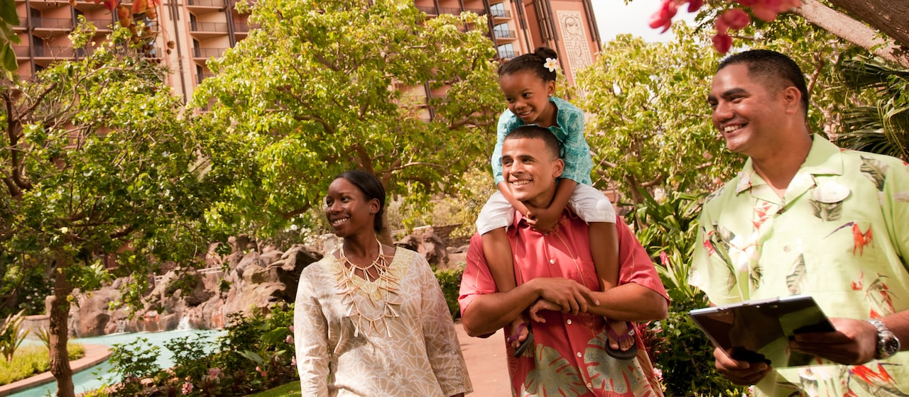 A Disney Vacation Club Guide shares a laugh with a family of 3, including a young girl who sits on her dad's shoulders